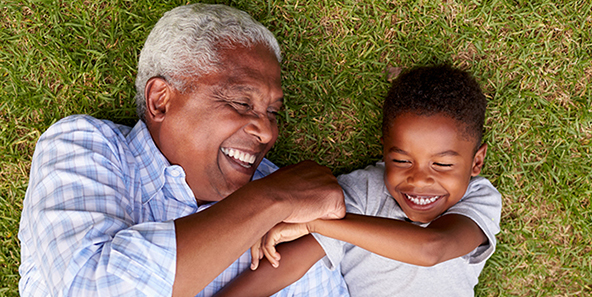 Philadelphia Medicare Health Plan Recipient And Grandson Smiling While Lying On The Grass