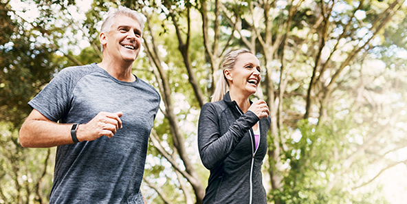 Couple Who Just Chose Their Medicare Plan Jogging Through The Trees